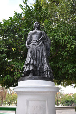 A statue of Carmen stands near the riverside