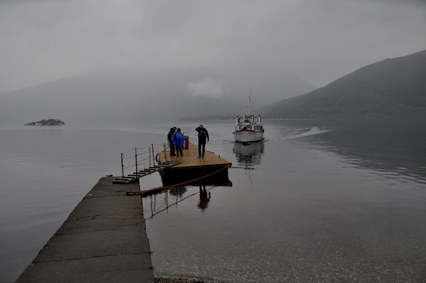 While waiting for the ferry to arrive at Rowardennan, passengers swipe midgies away.